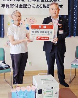 目録を手にする齋藤局長と山下理事長/下は寄贈された発電機
