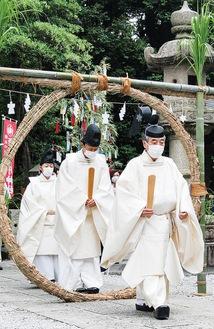 境内に置かれた茅の輪をくぐる石川宮司(先頭)