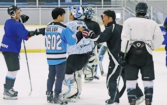 練習を終え拳を合わせる小塚さん(左から2人目)と浅沼監督ら