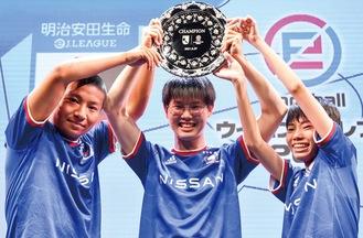 優勝トロフィーを掲げる(左から)徳地さん、外山さん、白鳥さん(C)J.LEAGUE/(C)Konami Digital Entertainment