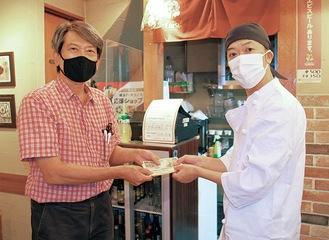 見舞金を手渡す、田中会長(左)と「とんかつ かつき」の金子オーナー