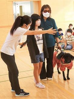 碇谷さん(右)に肩を貸し先導する児童(中央)。左は橋爪さん