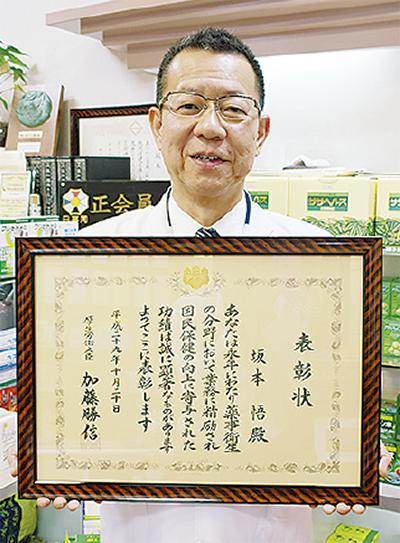 表彰状を手にする坂本氏