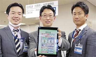 配信が始まったアプリをPRする港北区役所の橡木誠司さん(中)と佐藤大介さん(左)、杉本悟史さん