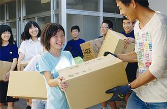 川和中で支援物資を運ぶ児童ら