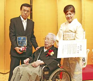 旭日単光章受章祝賀会の中で区民栄誉賞が贈られた。親族に囲まれる保氏(中央)。