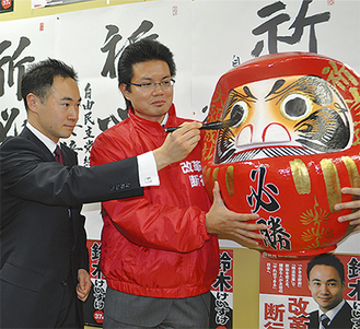 当選後ダルマに目を入れる鈴木氏(左)
