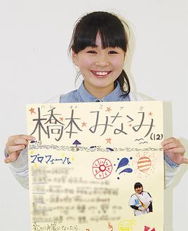 広報ポスターを掲げ、笑顔の橋本さん