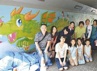 壁画の前に集まった新栄高生徒と地域関係者ら