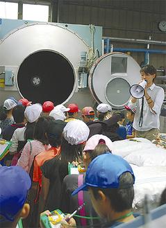 工場内の機械を説明する動夢企画の九鬼代表