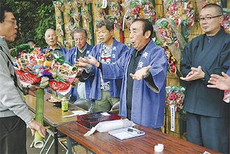熊手の購入者に対し、一本締めを披露する八木住職(右)と世話人ら