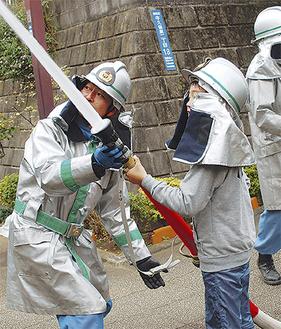 小学生の放水体験を補助する消防団員(左)=2日撮影
