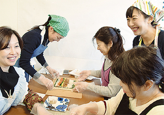 参加者と調理する石川さん(右)