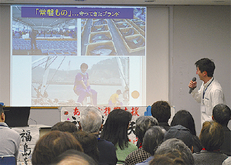 写真を見せながら現状を話す菊地さん(右)=5日