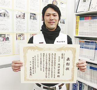 「全日本ベスト塗装店賞」の賞状を手にする、青葉店の上尾政裕さん