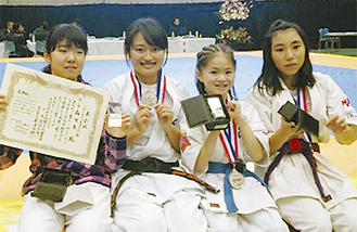 左から全国大会出場を決めて賞状やメダルを手にする森さん、東さん、溝上さん、望月さん=空手道MAC提供
