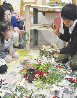 花かんむりの作り方を指導する宮原店長(右)