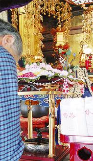 お釈迦様の像に甘茶をかけ、手を合わせる参拝者