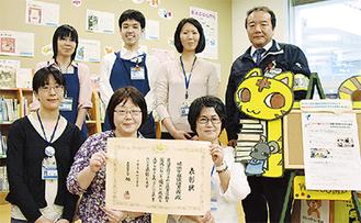 表彰状を手にする職員と三田館長(後列右)
