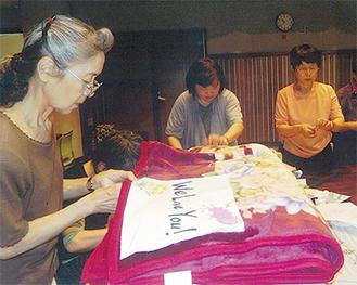 毛布にメッセージを縫い付ける参加者ら=吉川さん提供
