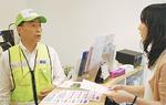 エキニワ北山田内の店舗にチラシを配布する鏑木会長(左)