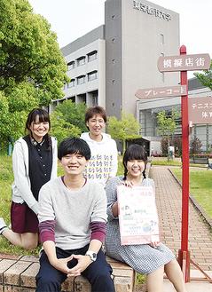 手作りの指示板と並ぶ島津会長(前列左)と運営委員のメンバー