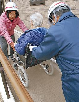 車いすに乗せた入居者を搬送する町内会員