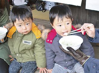 「おいしい」と粥を食べる子どもたち