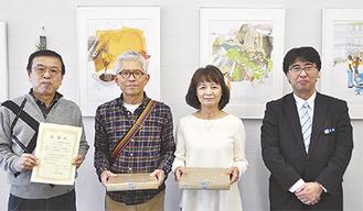 金子会長(左)と展示している河合夫婦、平野支店長