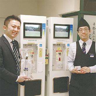 サーバーの前でH2‐BAGを持つ同社の小菅さん(左)と東急百貨店の末吉さん
