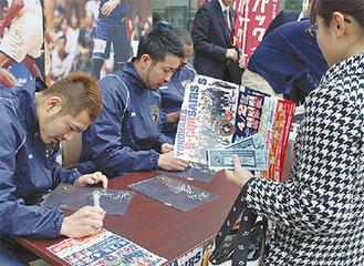 チケットを購入したファンにサインする選手たち