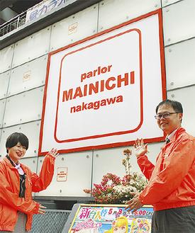 店外で笑顔を見せる伊澤店長(右)とスタッフ