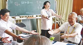 大棚カフェで座ったまま体操をする畑澤区長(左)ら