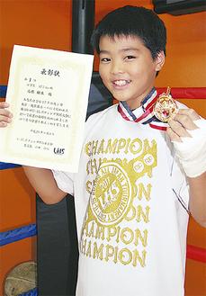 金メダルと表彰状を手にする高橋樹生君