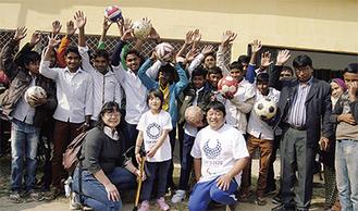 ボールを手に笑顔の現地生徒らと内野さん一家(前列)