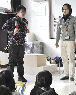 廻し地蔵を背負う教諭(左)と羽毛田さん