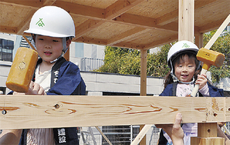 建築職人と一緒に家を造る子ども