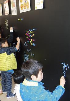 新しい黒板に絵を描く子ども