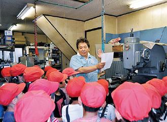 プレス加工工場で話を聞く児童