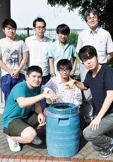 古川准教授(後列右)と廃食用油を樽に注ぐ学生ら