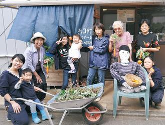 菊島さん(右)小室さん(左)と採れたて野菜を持つチャコ村に集まった人