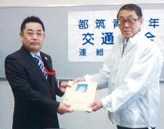反射材を手渡す鴨志田会長と木本局長(左)=都筑署提供