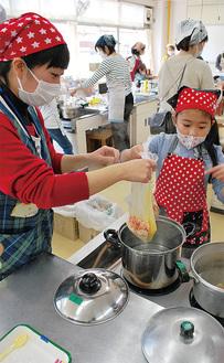 炊き込みご飯入りの袋を鍋に投入する親子
