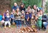 掘ったタケノコを持つ親子とすくすくサロンの福田代表(後列左)
