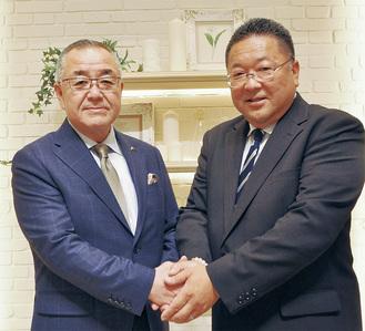 栗林前会長(左)と固い握手をする木伏新会長