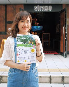 会場の前でポスターを手にする大嶋さん