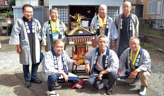 新しい子ども神輿を囲む保存会メンバーと三田会長(前列左)、金子さん(前列中央)