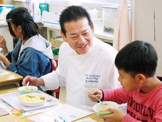 給食を楽しむ児童と中塩シェフ(中央)