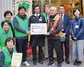 サロンのポスターを持つ東急ストアの中村副店長(中央)と折戸会長(右)、齋藤事務局長ら参加したメンバー