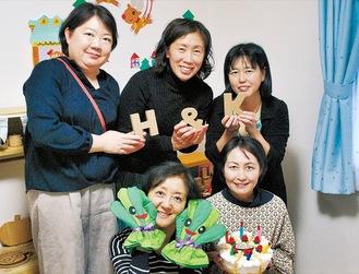 手作りの遊び道具を持つ中尾さん(下段右)とスタッフ